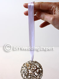 adding ribbon to a wedding pomander ball